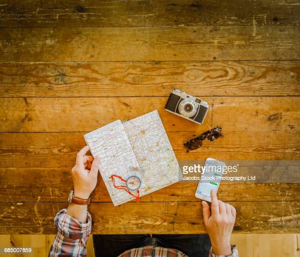 Caucasian man using cell phone and map on wooden table