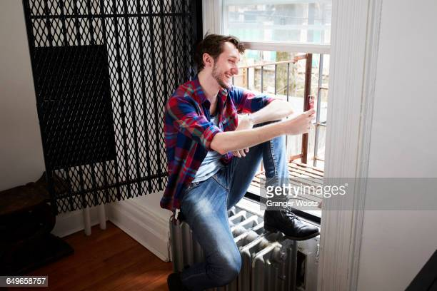 caucasian man using cell phone in window - one young man only stock pictures, royalty-free photos & images