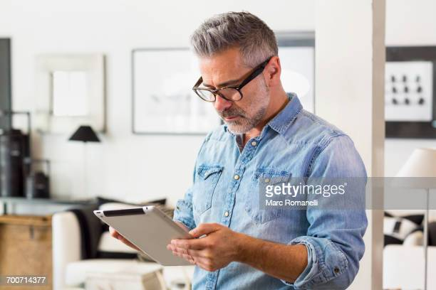 Caucasian man using digital tablet in livingroom