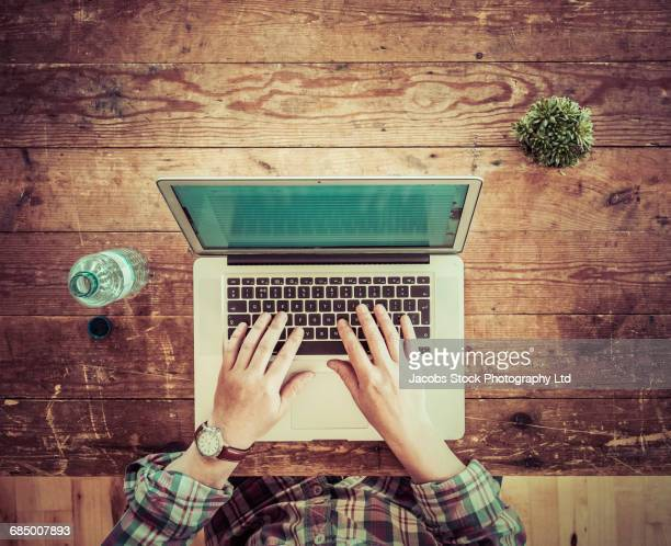 Caucasian man using laptop at wooden table