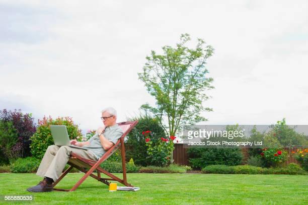 Caucasian man using laptop in lawn chair in backyard