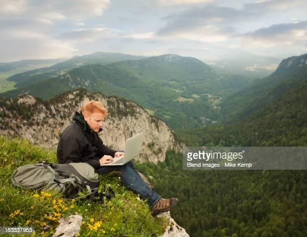Caucasian man using laptop on remote cliff's edge