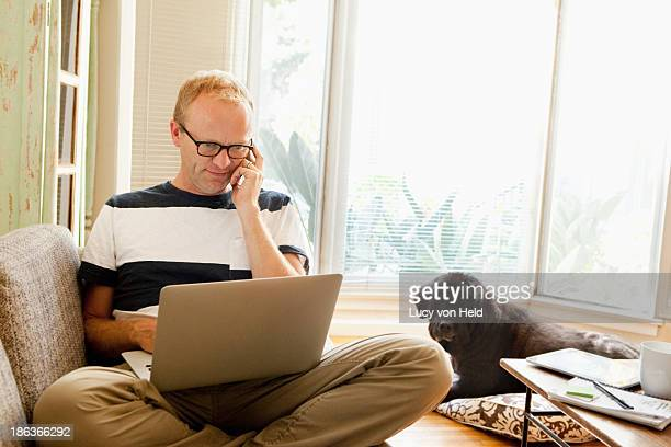 Caucasian man using laptop on sofa