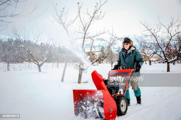 caucasian man using snow blower in snowy field - schneefahrzeug stock-fotos und bilder