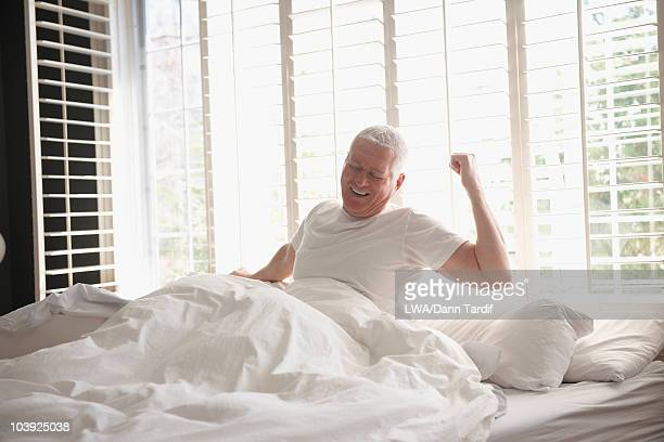 Caucasian man waking in bed
