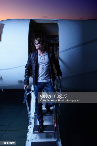 Caucasian man walking down steps of private jet