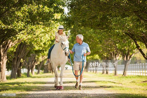 Caucasian man walking horse with granddaughter