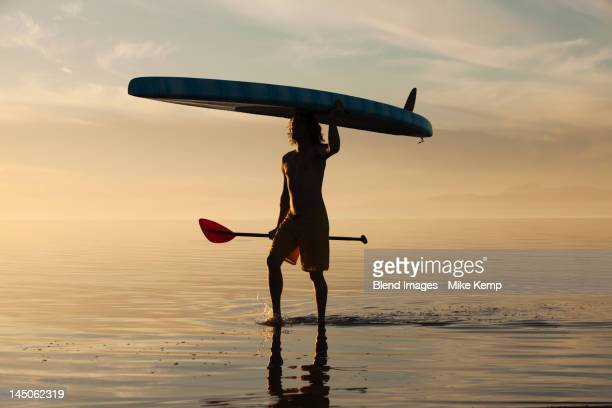 Caucasian man walking in water carrying paddle board