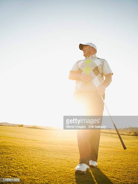 Caucasian man walking on golf course with golf club