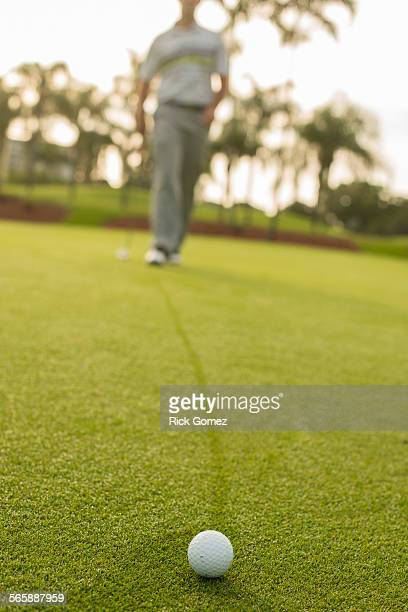 Caucasian man walking to golf ball on golf course green