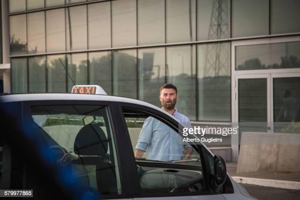 Caucasian man walking towards taxi
