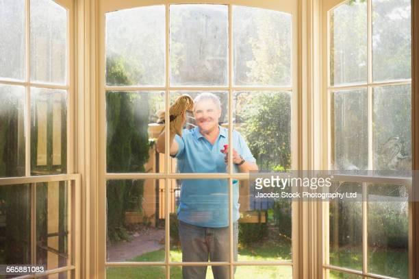 Caucasian man washing windows