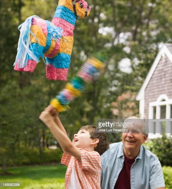 Caucasian man watching grandson hit piûata