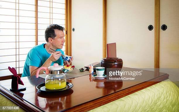 Caucasian man watching media on laptop in Japanese  room