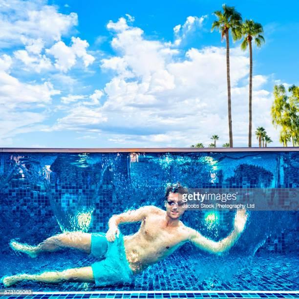 Caucasian man waving in swimming pool