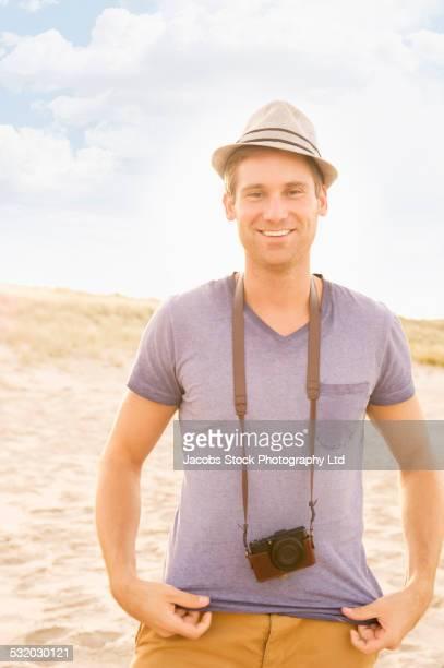Caucasian man wearing camera strap on beach