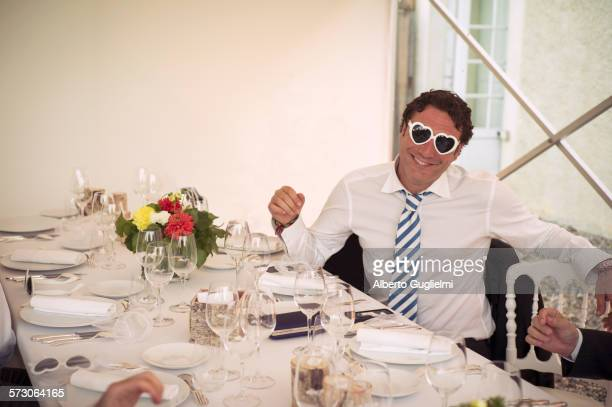 Caucasian man wearing heart-shaped glasses at table
