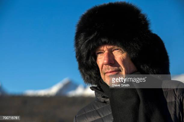 caucasian man wearing scarf and fur hat in winter - fur hat stock photos and pictures