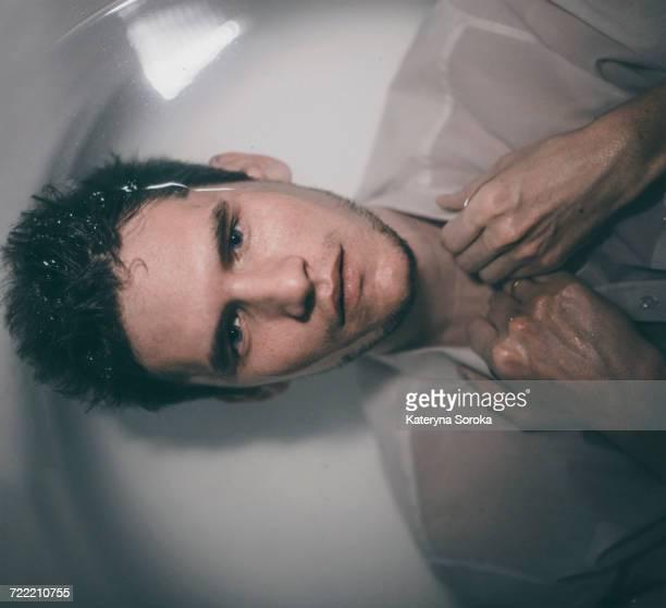 Caucasian man wearing shirt laying underwater in bathtub