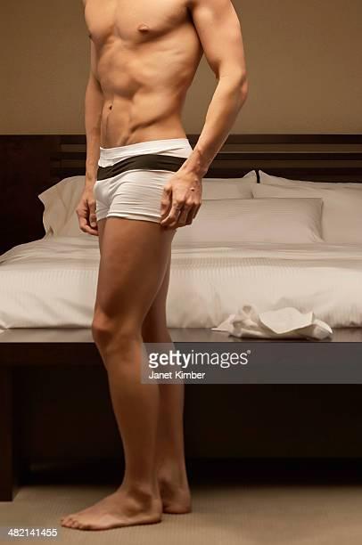 Caucasian man wearing underwear in bedroom