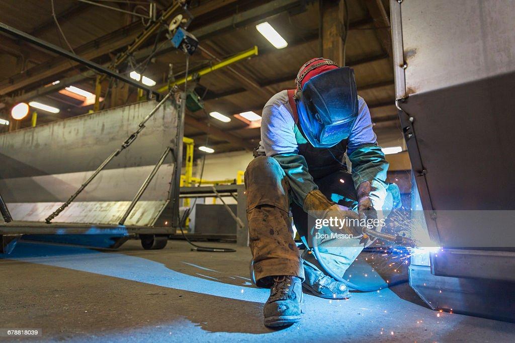 Caucasian man welding metal in factory : Stock Photo