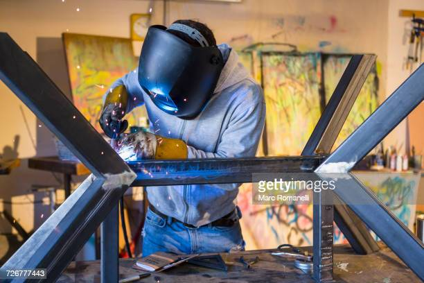 Caucasian man welding metal sculpture