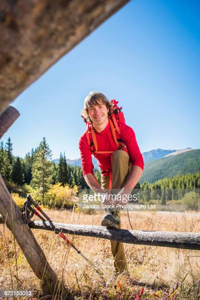Caucasian man with backpack leaning on fence tying shoelace