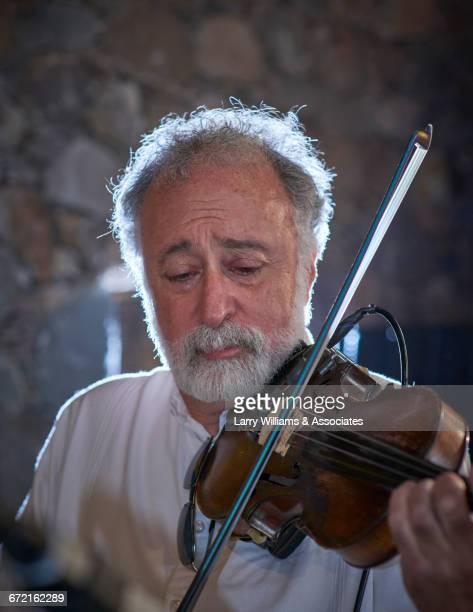 Caucasian man with beard playing violin