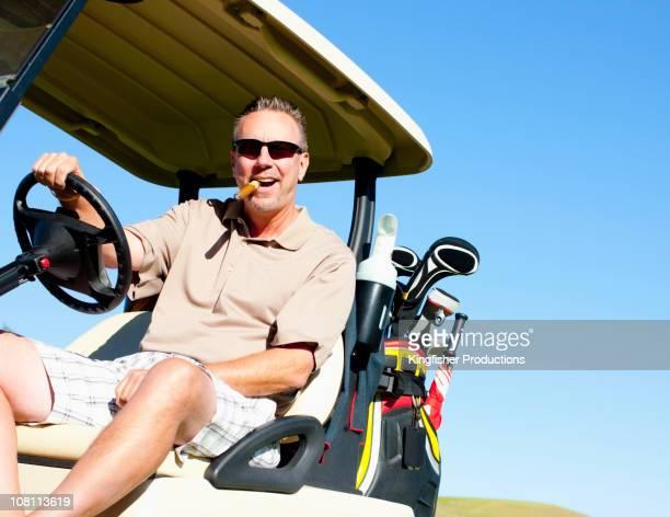 白人男性、シガーゴルフ練習場のゴルフカート