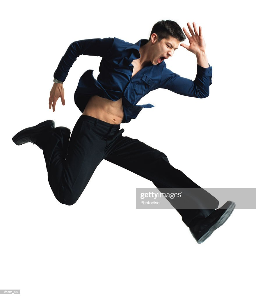 caucasian man with dark blue button down shirt and black pants jumping and running with angry look on his face and arms flailing : Foto de stock