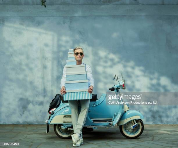Caucasian man with gift boxes on vintage scooter