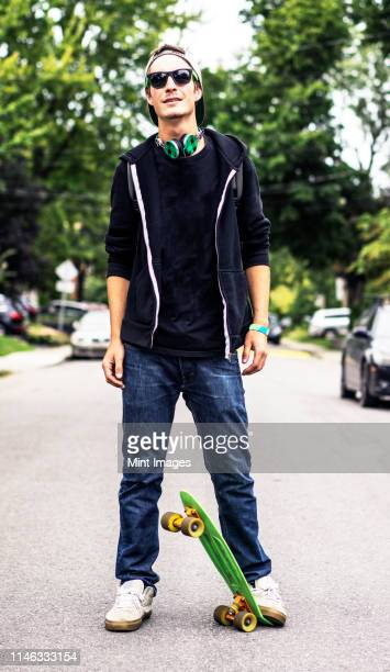 caucasian man with headphones standing on skateboard - só homens jovens imagens e fotografias de stock