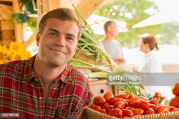 caucasian man with produce at farmers market - bancarella di verdura foto e immagini stock