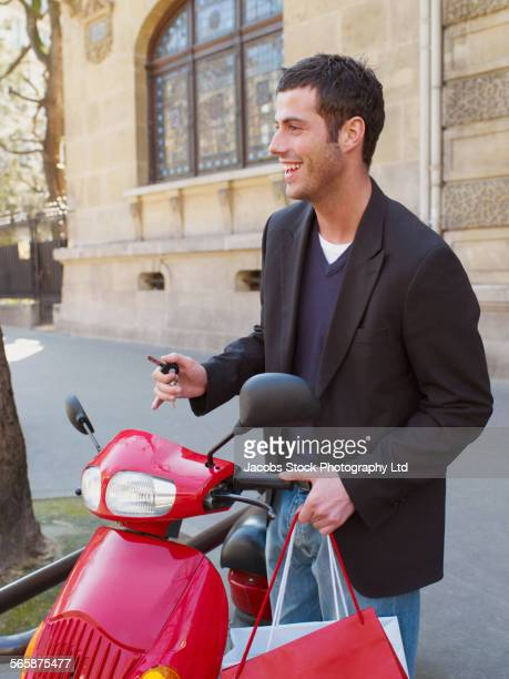 Caucasian man with red scooter on city sidewalk