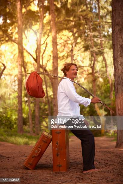 Caucasian man with suitcases and bindle in forest
