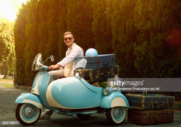 Caucasian man with suitcases driving vintage scooter