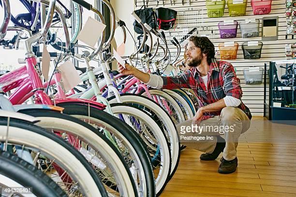 Caucasian man working in bicycle shop