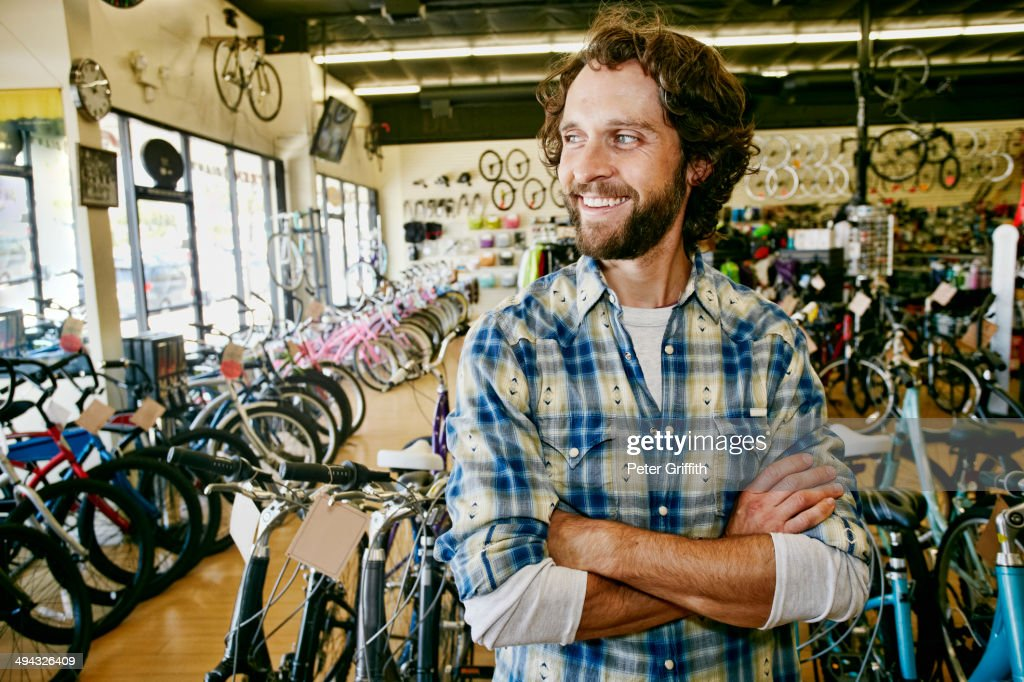 Caucasian man working in bicycle shop : Stock Photo