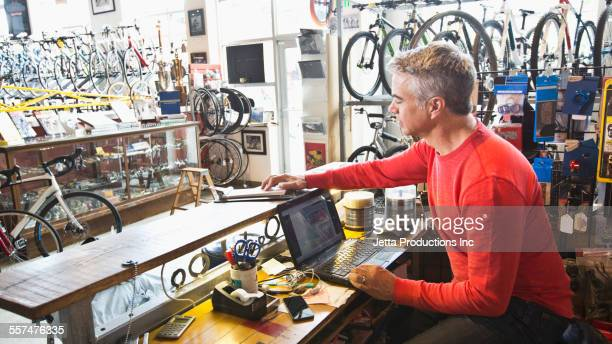 caucasian man working on laptop in bicycle shop - sportgeschäft stock-fotos und bilder