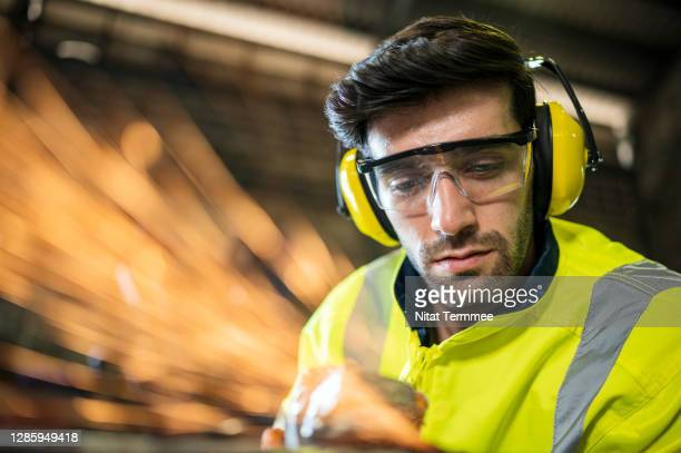 caucasian manual worker using circular saw to grinding metal work pieces in metal industry. - ear protection stock pictures, royalty-free photos & images