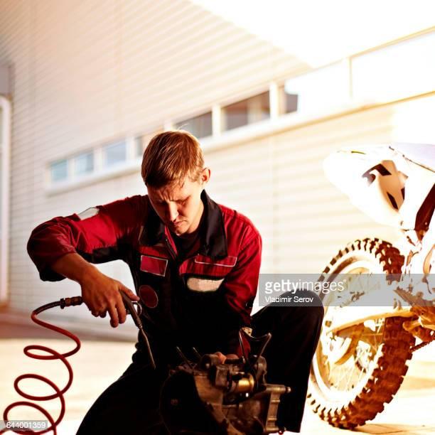 Caucasian mechanic examining motorcycle parts