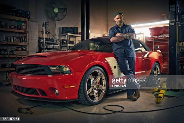 Caucasian mechanic posing on red sports car