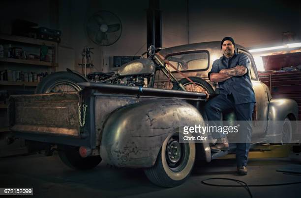 Caucasian mechanic posing on vintage truck with motorcycle