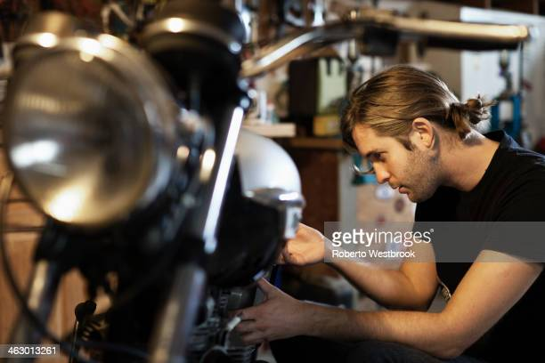 Caucasian mechanic working on motorcycle