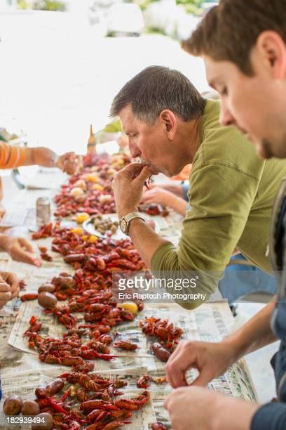 Caucasian men eating at crawfish boil
