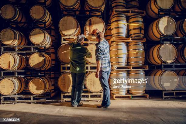 caucasian men examining barrel in distillery - viniculture stock pictures, royalty-free photos & images