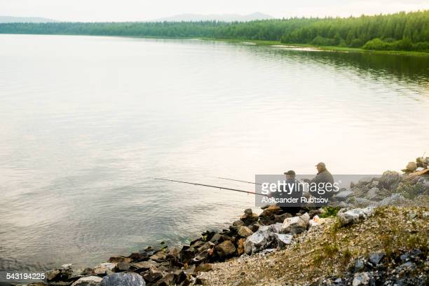 Caucasian men fishing in rural lake