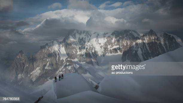 Caucasian men hiking on mountain in winter