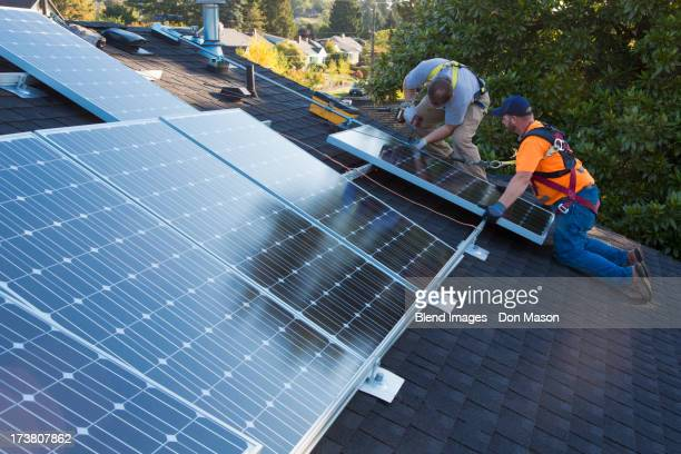 Caucasian men installing panels on roof