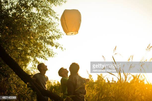 caucasian men launching floating lantern outdoors - releasing stock photos and pictures